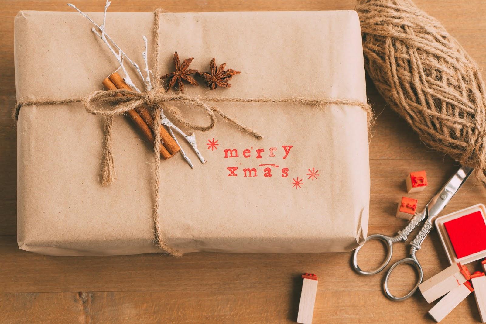 envoltorio de regalos con papel kraft, cuerda y rama de canela