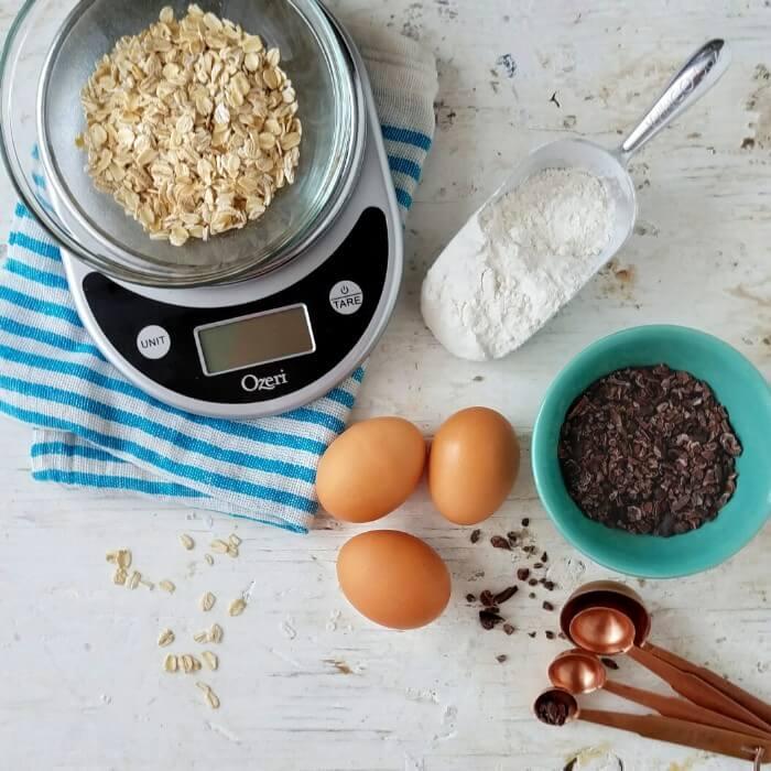 Ingredientes sobre una superficie: huevos, hojuelas de avena en una balanza, nibs de cacao, harina de trigo