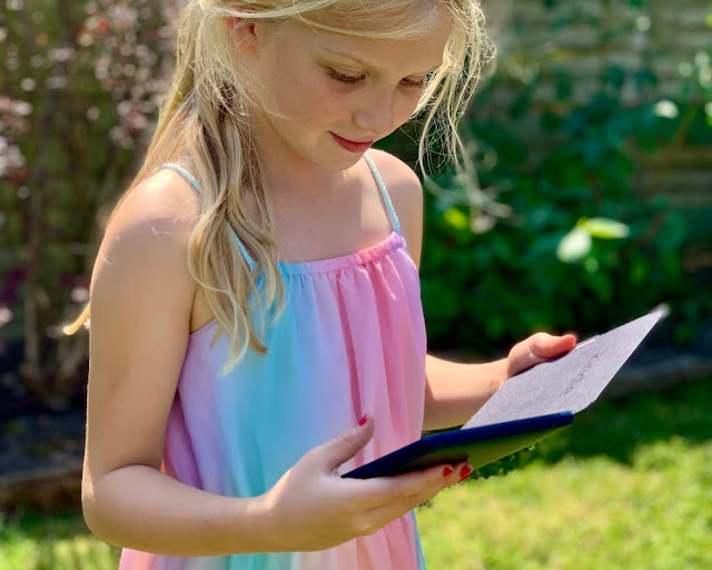 A 7 year old girl reading a Kindle in the garden. She is wearing a summer dress and has long blonde hair