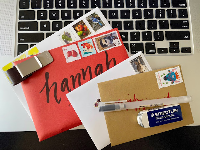 A stack of letters laid out on a laptop keyboard, with a variety of stamps and lettering styles