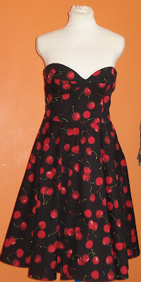 Tailors dummy wearing a strapless 50's style dress with red cherry print and boned bodice.