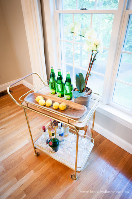 Gold and Glass Bar Cart perfect for living room decor with Selter, liquor bottles, glasses and lemons