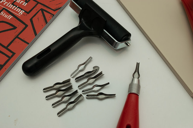 Lino printing roller and lino cutter with blades.