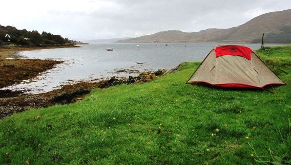 A tent pitched on the banks of a highland loch