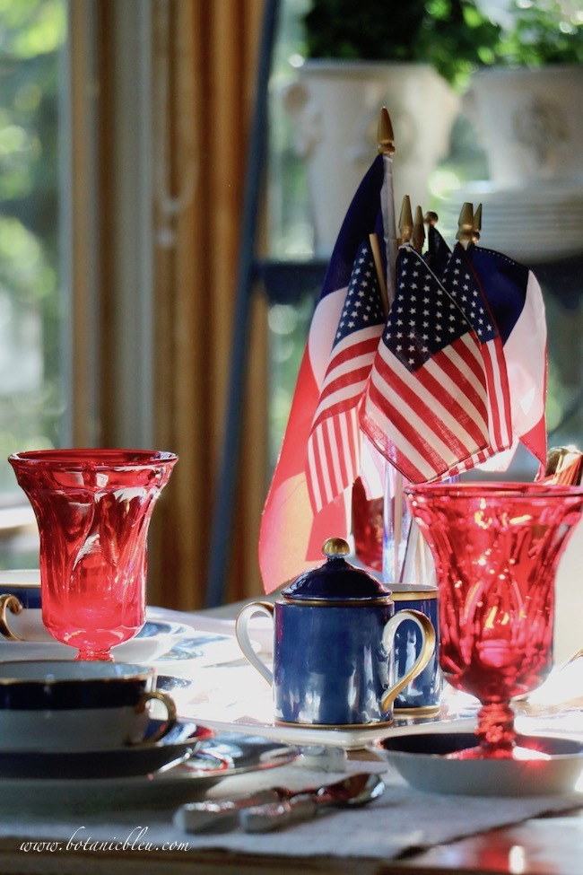 Labor Day patriotic French Country table setting with late sunlight streaming onto red glasses
