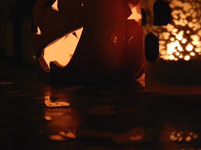 a pumpkin and ghost candle holder.