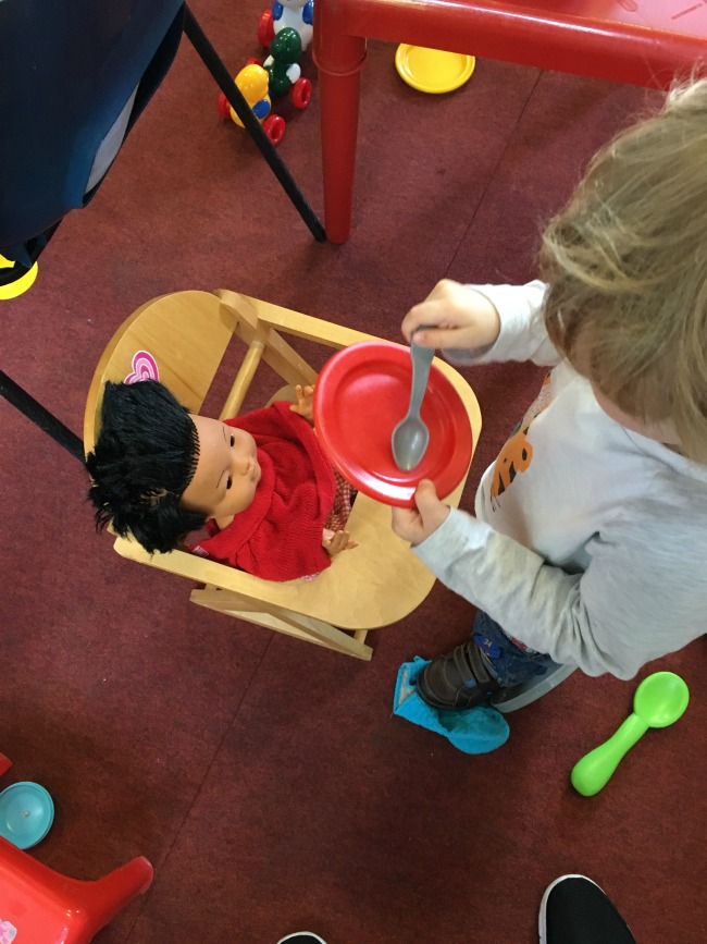 toddler with spoon and plate feeding doll in highchair