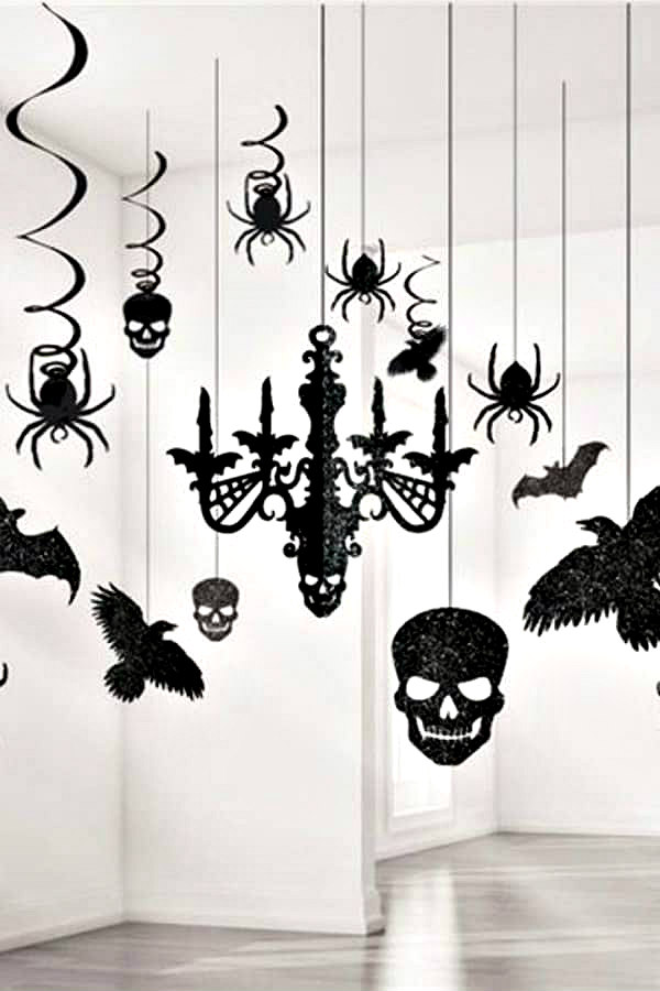 black glitter paper bat, spider, skull, and chandelier decorations hanging from ceiling
