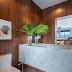 Lavabo sofisticado com paredes revestidas de madeira e bancada com cuba esculpida em pedra!