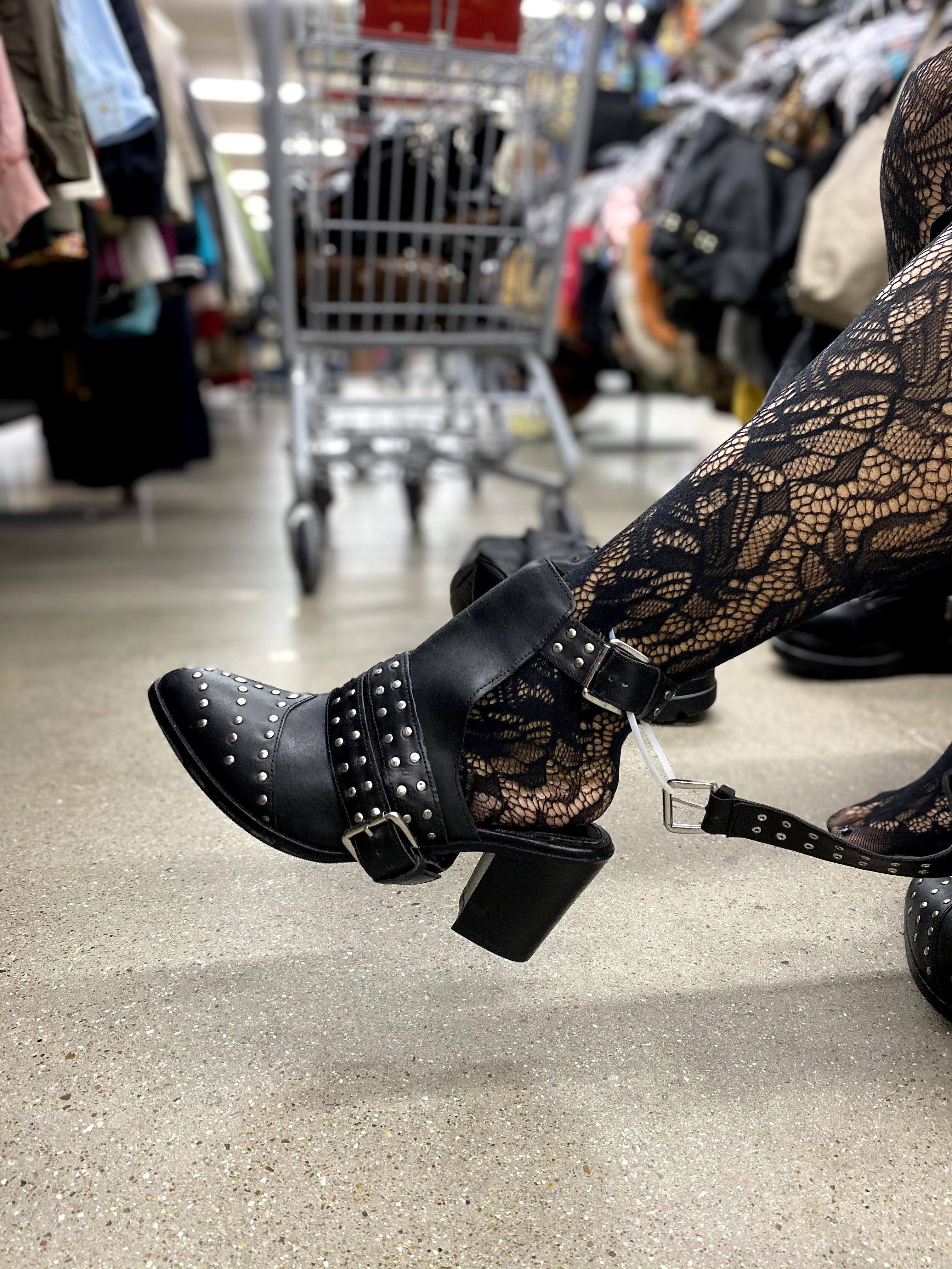 Woman showing off her thrift shoes from the vintage store.