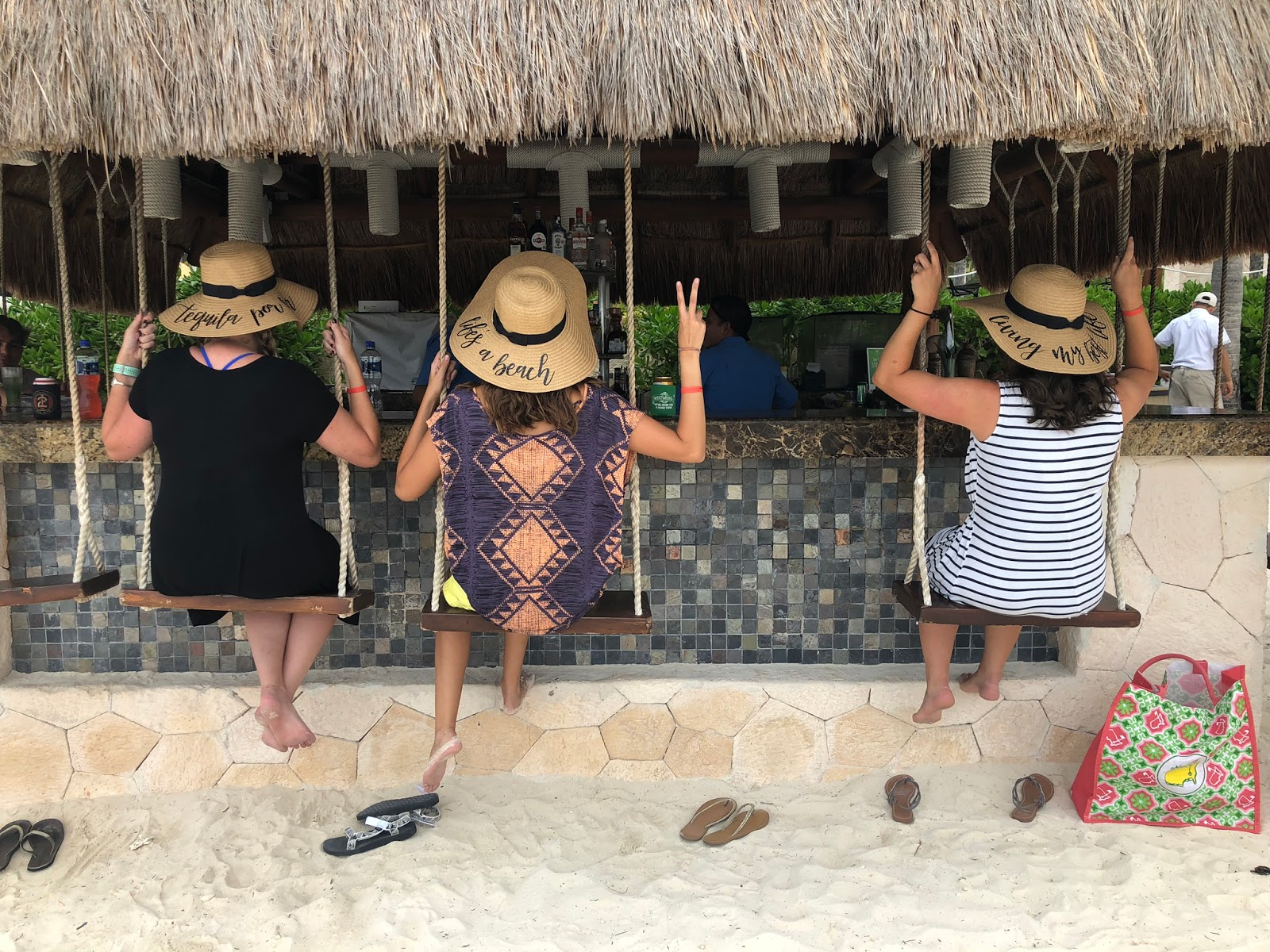 three women sitting at a bar with swings instead of barstools, their backs are to the camera and they're wearing the matching floppy beach hats