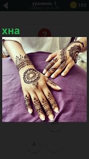 Показаны женские руки, на которых нанесен рисунок хной