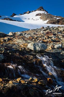 Sahale Peak above a rushing stream at a high camp in North Cascades National Park, Washington, USA.