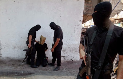 Hamas militants prepare to execute a person suspected of collaborating with Israel in Gaza City on Aug. 22, 2014.