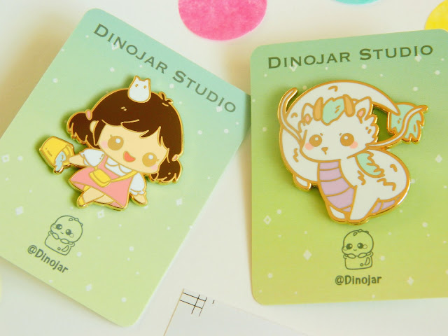 A photo showing two enamel pins by Dinojar. They are of the Studio Ghibli characters, Mei and Dragon Haku. They are backed on gold enamel and are super cute!