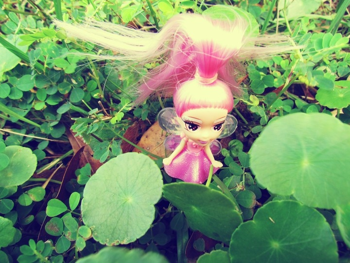 Pink fairy toy doll fairy with fairy wings in green grass and four-leaf clovers