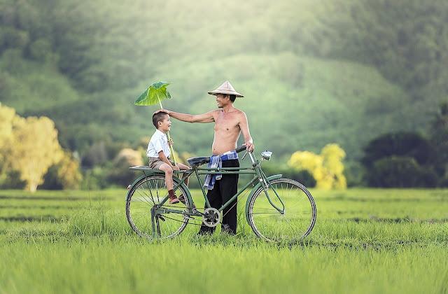 Pai e filho felizes na bicicleta