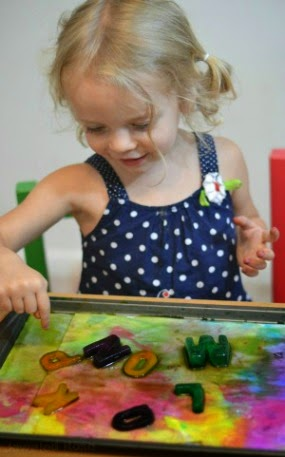 Painting with edible alphabet ice paints- a super fun Summer activity that is easy to set up, too!