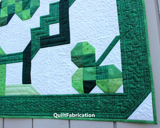 green three leaf clover in a quilt corner