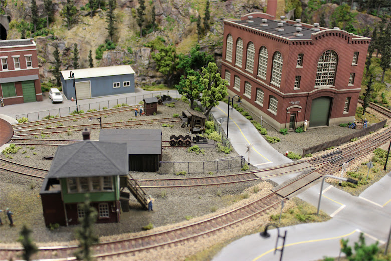 Industrial and railyard scene with grade crossings, turnout, signal tower and Northern Light & Power Co. kit