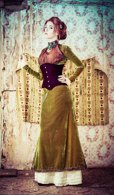 Girl wearing Steampunk clothing. Victorian influenced green velvet dress with corset and boots.