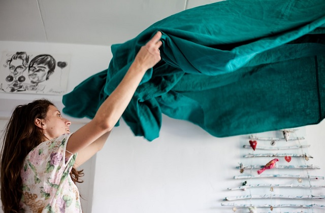 woman fixing bed sheet