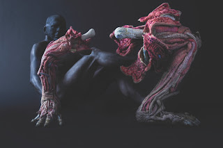 A darkly lit human body in the background is looking at what appears to be an arm and leg without skin, only bones, muscle, and nerves.