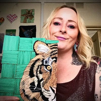 artist with quilled tiger wall art