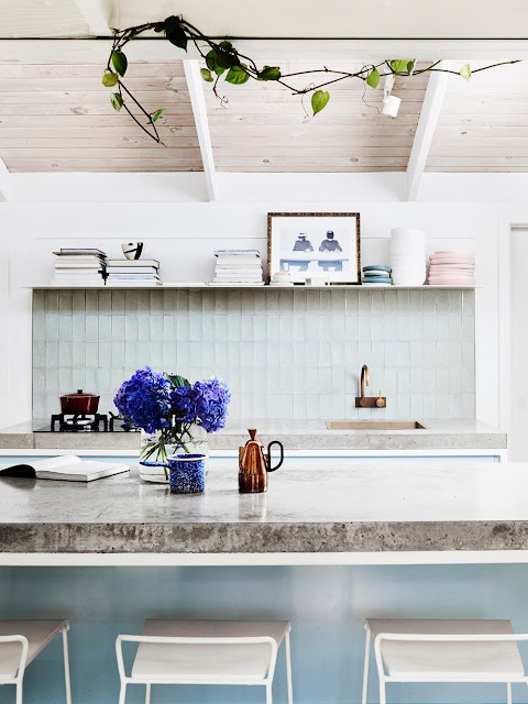 pale blue kitchen cabinets and shiny subway tile with black and white marble countertops