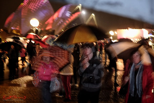 Umbrellas in the rain echoing the shape of the Sydney Opera House sails, Vivid Sydney 2013.