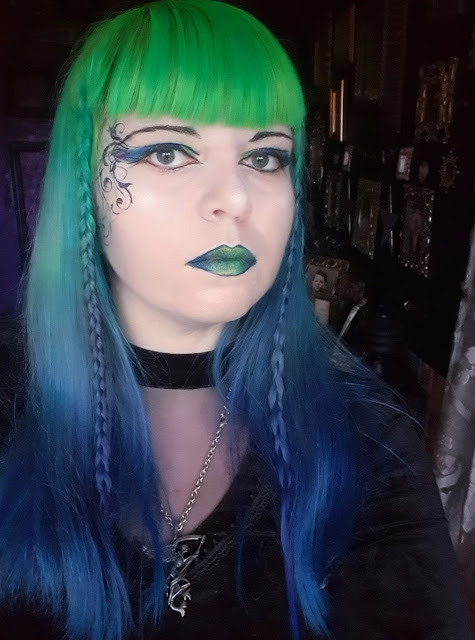 A woman with hair that is neon green at the top, in a gradient to royal blue at the bottom. Her hair is long, down to her bust, and she has a small braid either side of her face and a fringe. She is wearing heavy dramatic makeup in colours matching her hair - neon green, emerald green and tropical blue eye-shadow with black and violet winged eyeliner, metallic green lips lined in metallic violet, and ornate swirling vines down the right side of her face. She is wearing a black velvet top with a high neckline and a mesh v-neck cut out. She is wearing a pewter Alchemy Gothic pendant of the Grim Reaper with wings