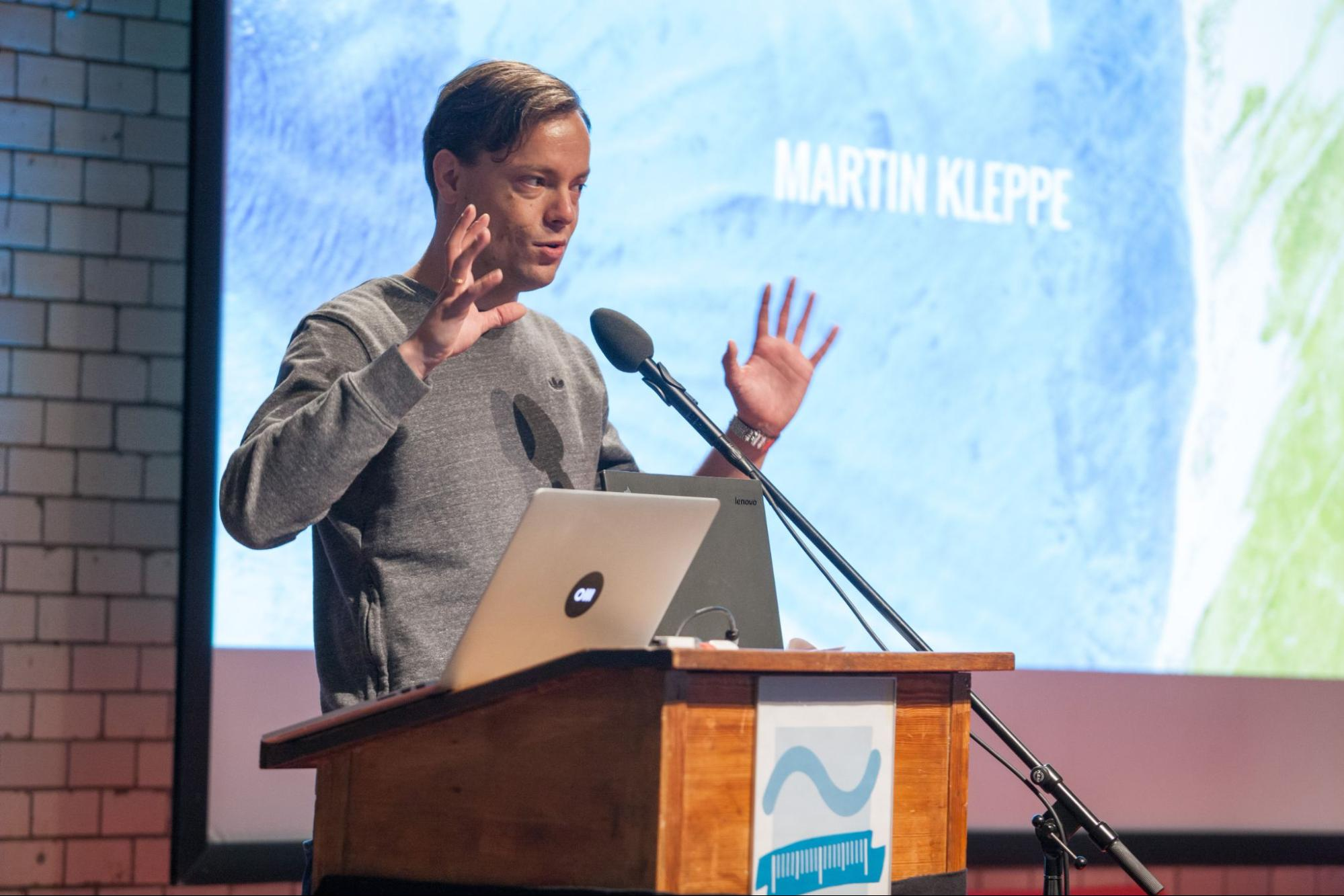 Image shows Martin Kleppe onstage behind his podium and laptop. His name is projected onto the screen behind him