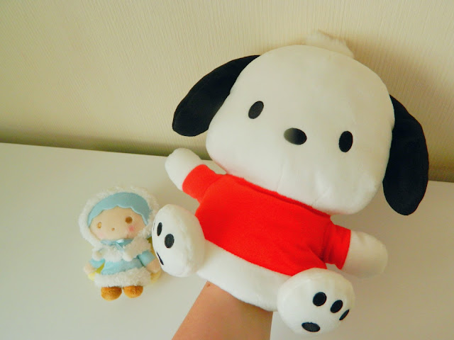 A photo showing a hand puppet of a puppy by the Japanese brand Sanrio, along with a small plush of a boy with blue hair