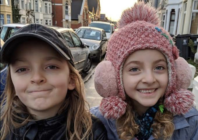 2 children in the street wearing hats and looking at the camera. Image from Our Transitional Life