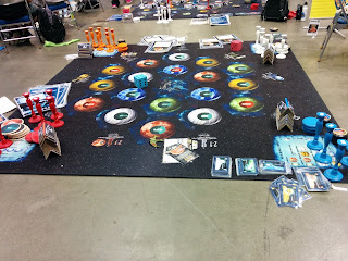 An oversized playset of Star Trek Catan. The board has been printed on a ten foot by ten foot carpet, and there are oversized cards and playing pieces around the edge of the board.