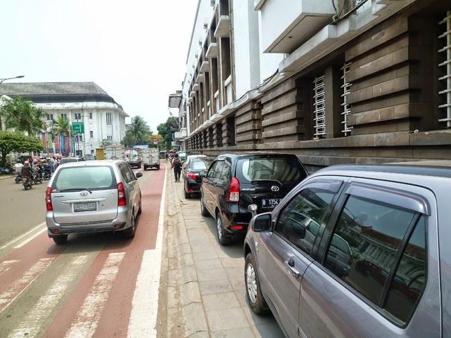 Coches aparcados en una acera de Yakarta