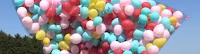 Hunderte bunte Luftballons schweben im Netz am Himmel.