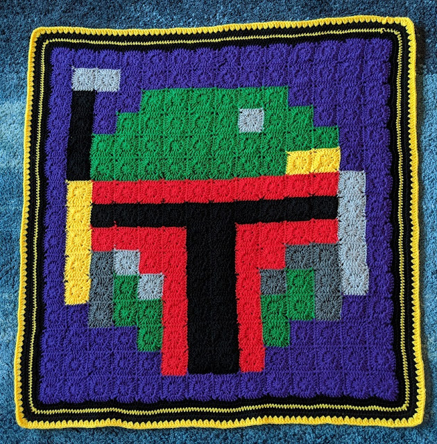 The finished blanket shown in full, small crochet squares sewn together to make pixel art of Boba Fett with purple background, and a border of black and yellow.