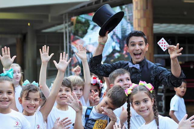 Mágico e crianças posando para foto em evento do dia das crianças em São Paulo.