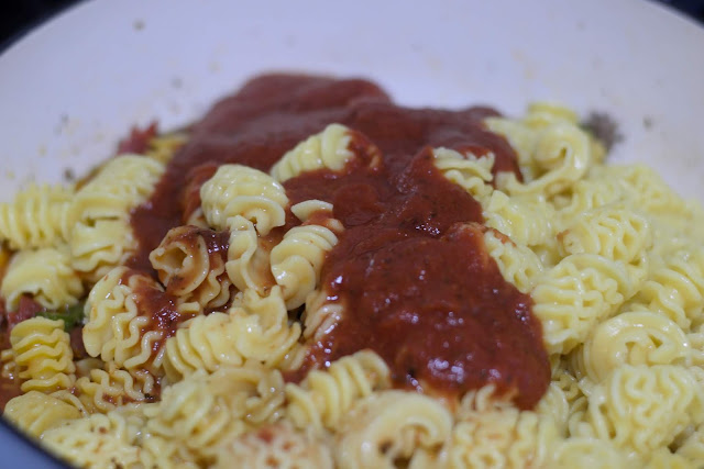 Pizza sauce poured over the pasta in the pan.