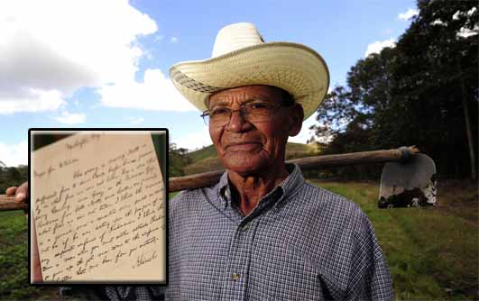 An old farmer with and axe on his shoulder standing in a plantation. A hand written letter in ink.