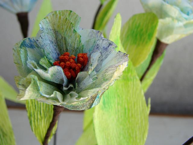 fiori di carta crespa e fiori secchi blu, arancio e foglie per un matrimonio green
