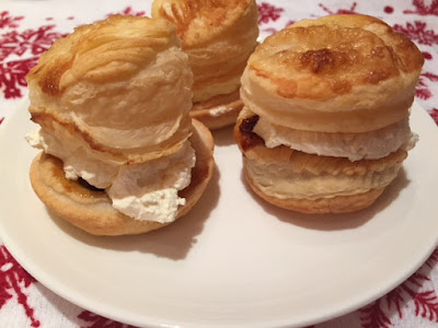 Three puff pastry mince pies filled with whipped cream on a plate- close up