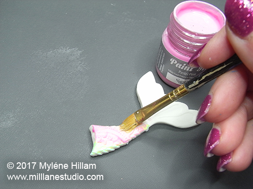 Painting the mermaid's tail with edible pink paint.