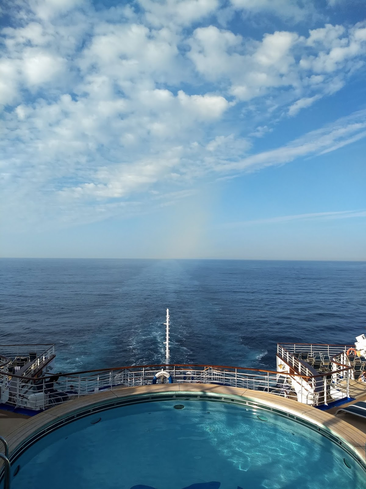 View of blue skies, a pool and the sea from the back of a cruise ship.