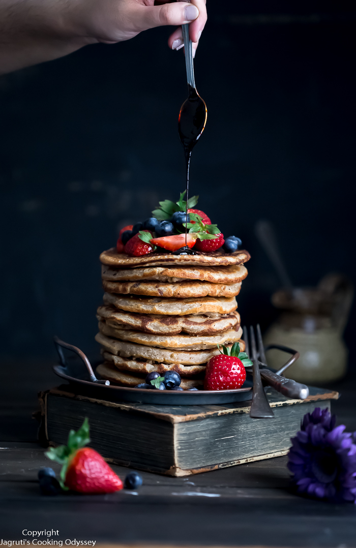 Picture of a stack of pancakes topped with strawberries and blueberries and pouring syrup