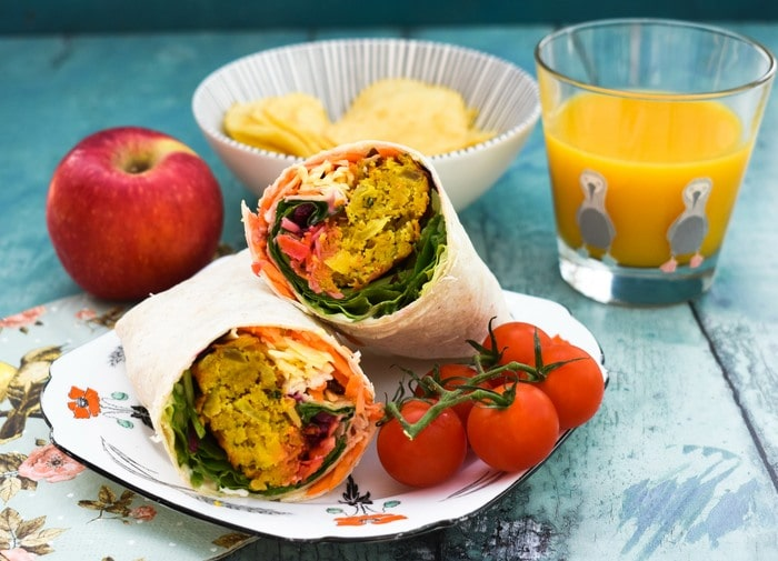 An onion bhaji lunch wrap, cut in half with filling showing on a floral square teaplate