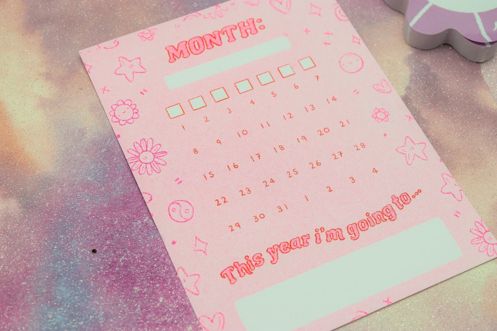 A close up of a monthly calendar post card. It is pink with neon pink outline.