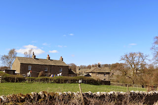 Stone cottages on the edge of the village, with washing drying on the line outside.