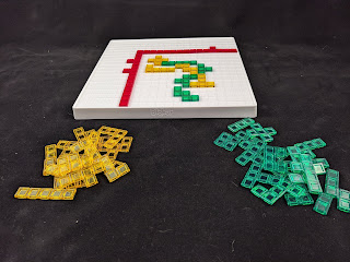 The same board as before, but with several rows and columns blocked off by a number of the red pieces to provide a smaller playing area, which is occupied by several of the yellow and green pieces, the unused of which are piled next to the board.
